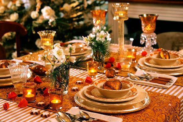 Хвоя в центре стола и свечи разной формы на новогоднем столе